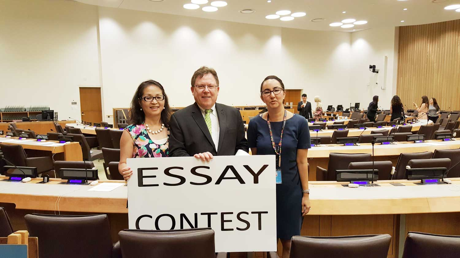 Photo: 3 adults in conference room with Essay Contest sign