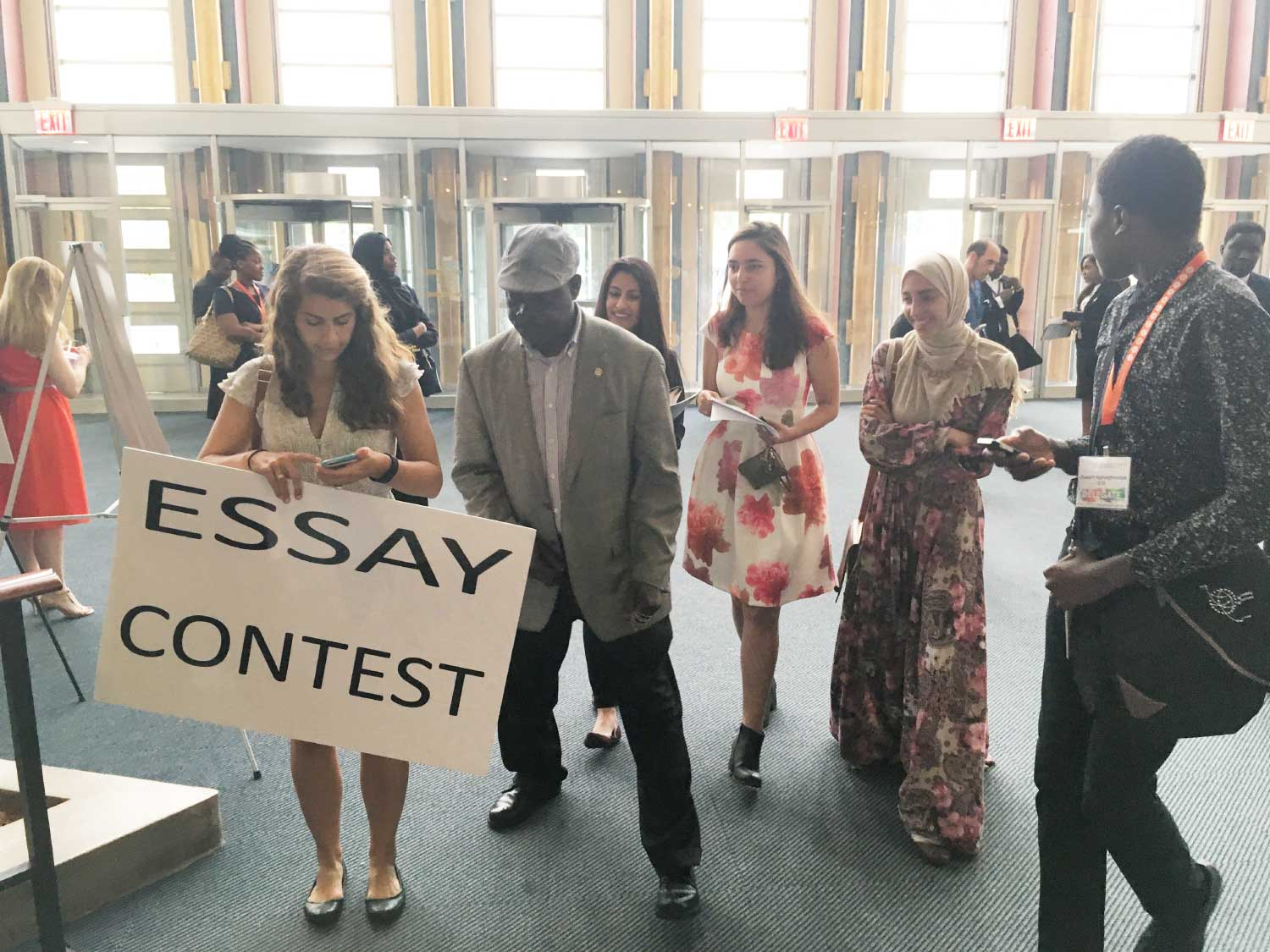 Photo: young people in lobby with Essay Contest sign